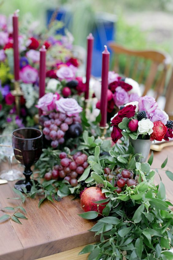 lush table decor of a foliage table runner dotted with grapes, plums and pomegranates plus jewel toned candles