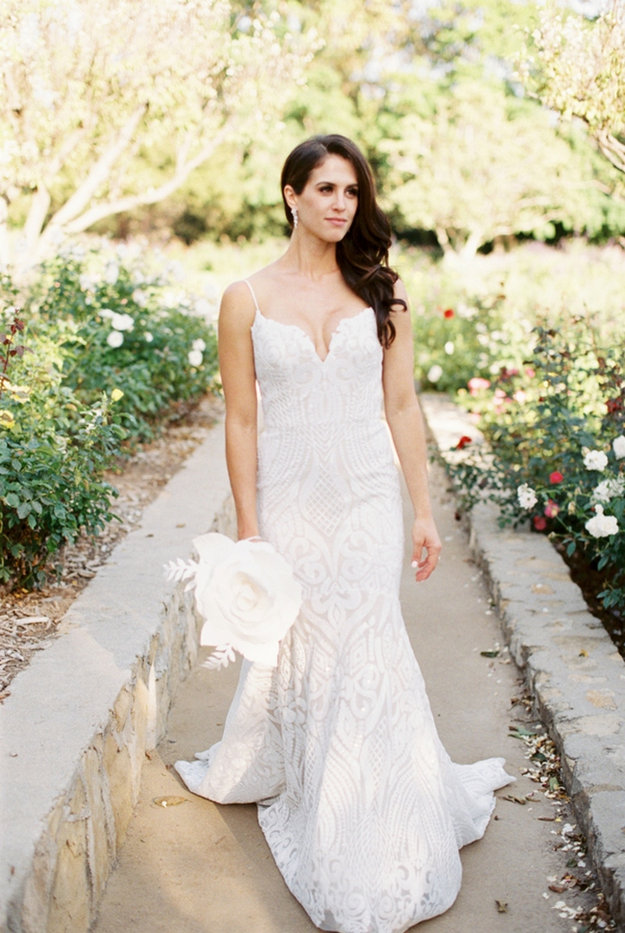The bride was wearing a sexy white lace sheath wedding dress with spaghetti straps and was carrying a white paper flower