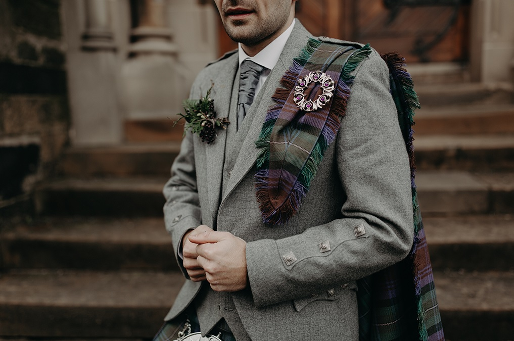 The groom was rocking his own kilt, a grey jacket, a grey vest and tie