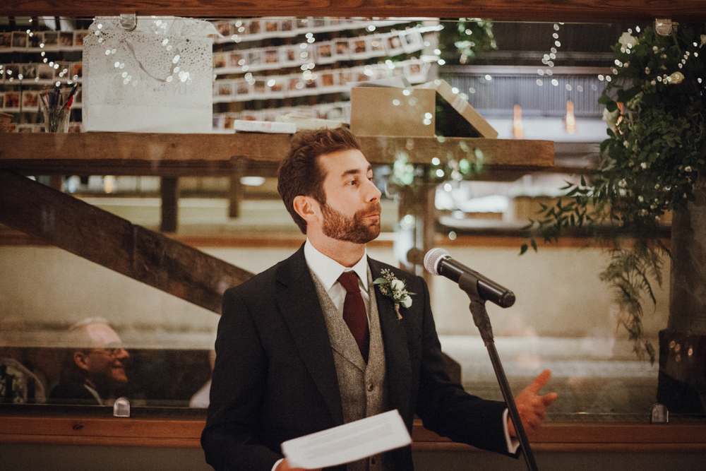 The groom was wearing a grey tweed suit with a neutral waistcoat and a knitted burgundy tie