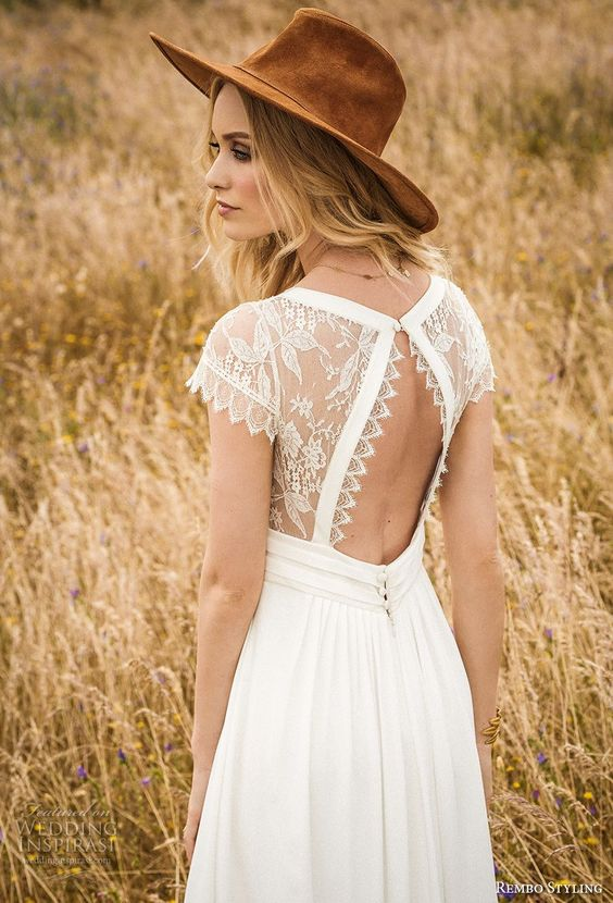 a boho A-line wedding dress with a lace cutout back and a brown hat for a stylish look