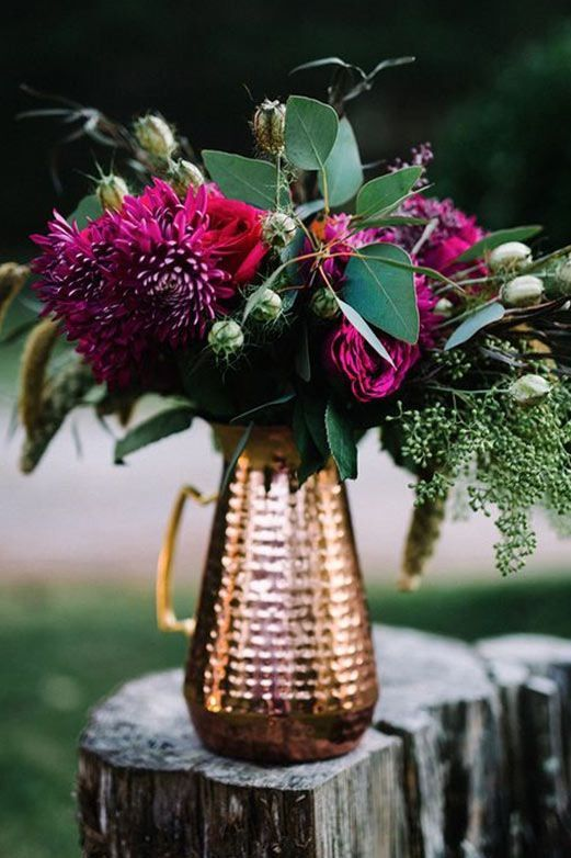 a chic fall wedding centerpiece of a copper pitcher, lush greenery and plum colored blooms for a wow look