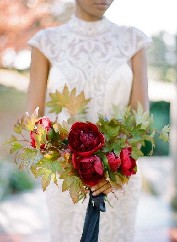a deep red wedding bouquet withh fall leaf accents and a navy ribbon looks bright and cool