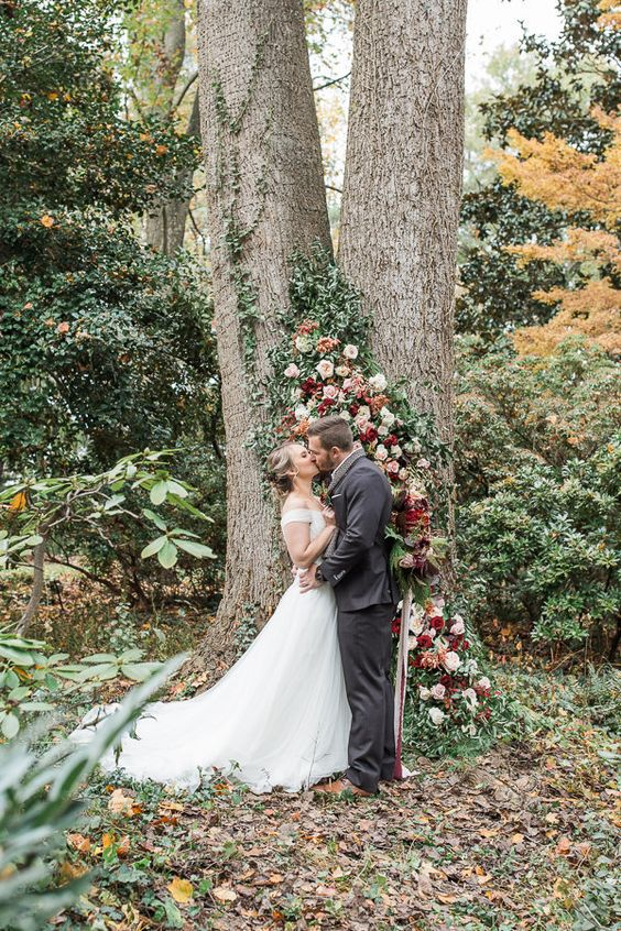 an elegant fall wedding backdrop of a living tree decorated with lush blooms and greenery