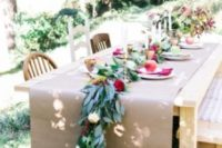 03 kraft paper instead of a tablecloth, a greenery dotted with bold and white blooms and gold candle holders