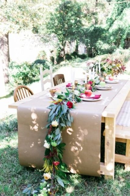 kraft paper instead of a tablecloth, a greenery dotted with bold and white blooms and gold candle holders