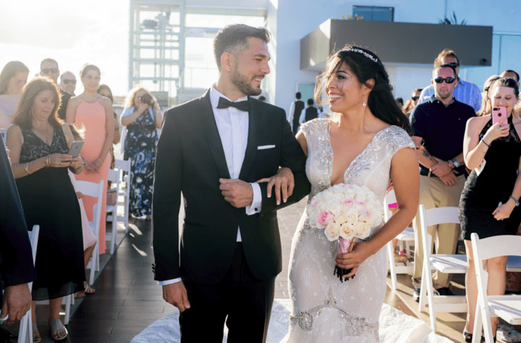 She was wearing a gorgeous lace embellished mermaid wedding dress with a plunging neckline and the groom opted for a black tux