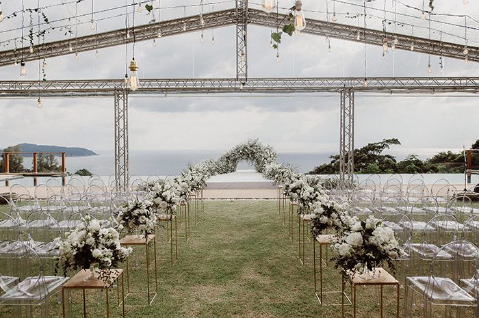 The ceremony space was a romantic outdoor one, with acrylic chairs, lots of white blooms and an ocean backdrop