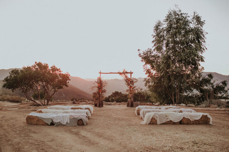 The wedding ceremony space was a boho rustic one with hay stacks and a cool  arch