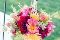 04 a bright floral arrangement in burgundy, pink  and yellow wth herbs in a mason jar