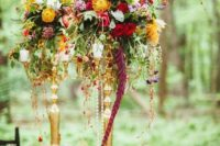04 a colorful floral centerpiece of cascading blooms and greenery of various colors for a woodland wedding