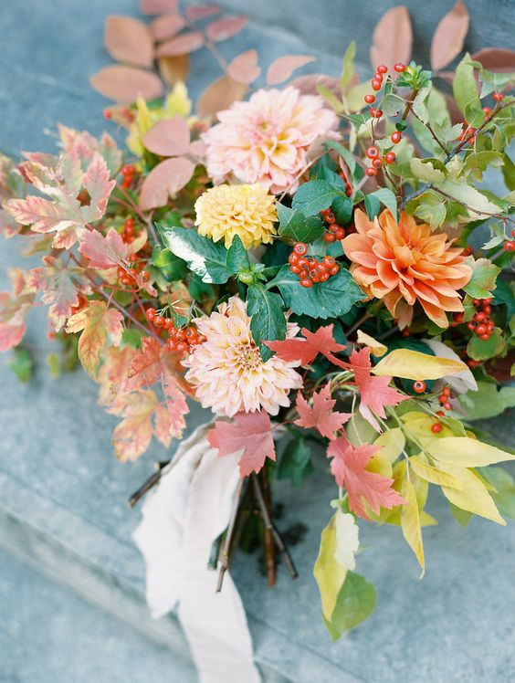 a fall leaf and bloom wedding bouquet with dahlias, fall leaves and berries plus a blush ribbon