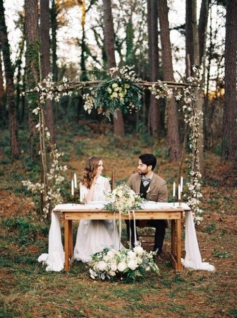 a woodland fall wedidng arch with white blooms, greenery and herbs for a textural look