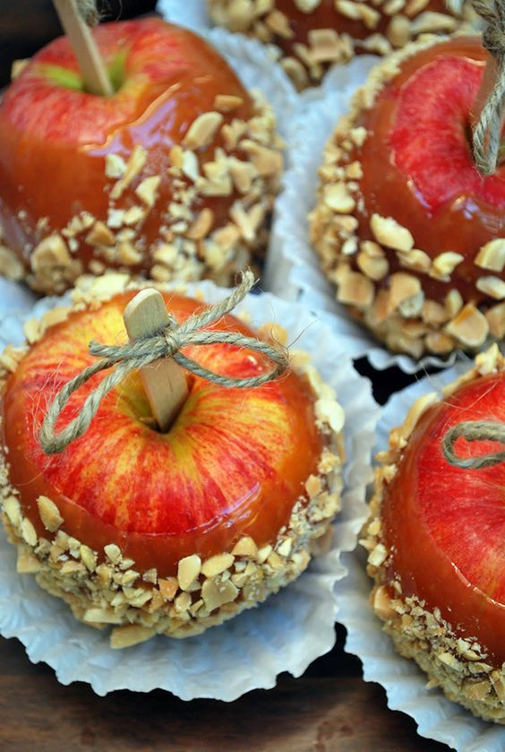 caramel and nut covered apples with tiny twine bows on top for a rustic fall wedding