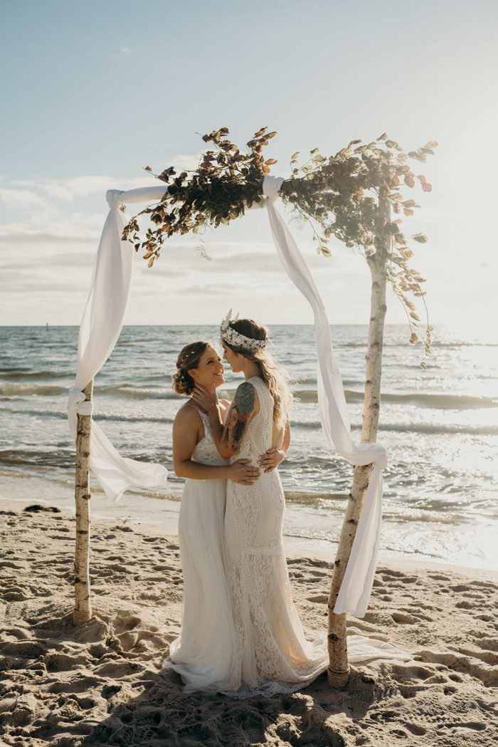 The couple echanged the vows under a romantic boho beach arch at the sunset