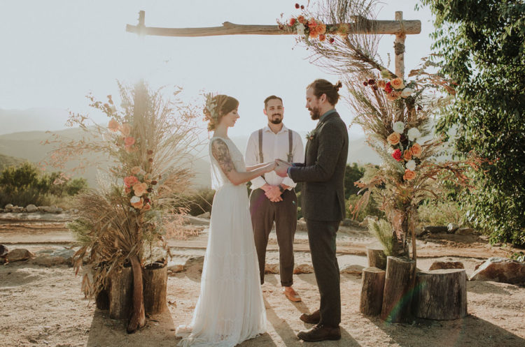 The wedding arch was decorated with herbs, leaves, colorful blooms for a cool boho look