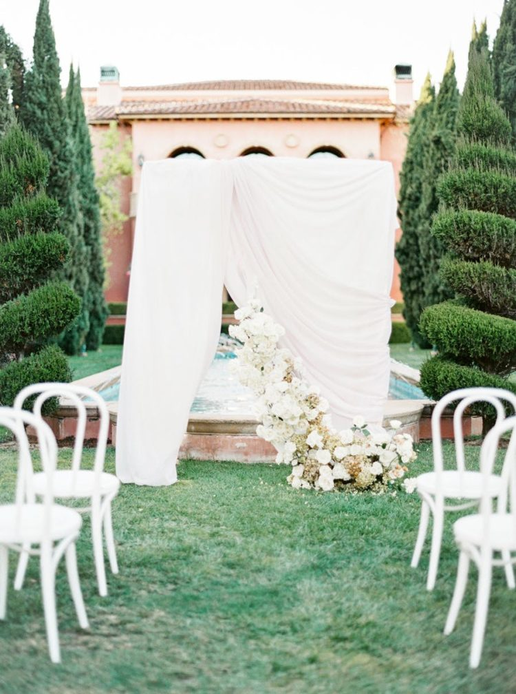 The wedding backdrop in blush was installed in front of a fountain and was decorated with lush blooms