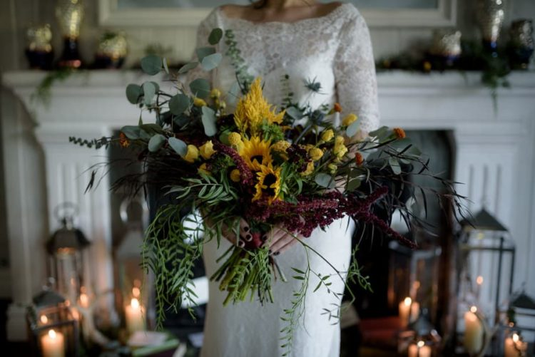 The wedding bouquet was done with textural and cascading greenery, burgundy and yellow blooms to embrace the fall