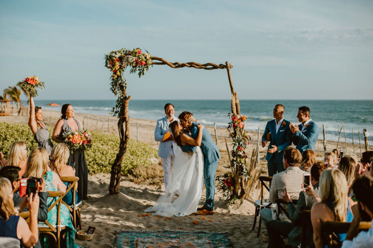 The wedding ceremony took place on the beach, the arch was amde of driftwood and decorated with bright flowers