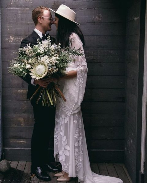 a boho bride wearing a lace dress with a train and a neutral hat for elegant boho-inspired look