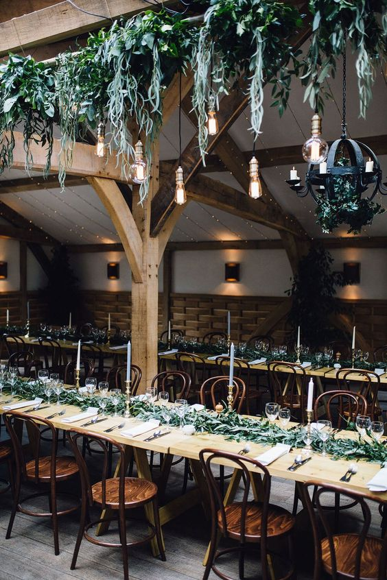 a creative cascading greenery overhead wedding decoration with bulbs hanging down and a matching greenery runner
