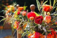 05 a fall arrangement of red, burgundy and orange blooms, green grasses and leaves in a jar