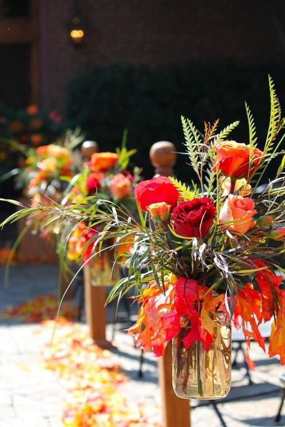 a fall arrangement of red, burgundy and orange blooms, green grasses and leaves in a jar