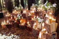 05 a fall woodland wedding backdrop made up of wood stumps, candles, white blooms and petals