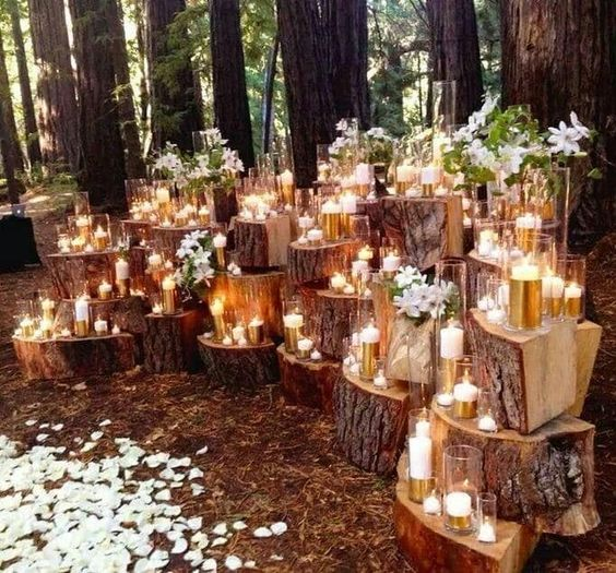 a fall woodland wedding backdrop made up of wood stumps, candles, white blooms and petals