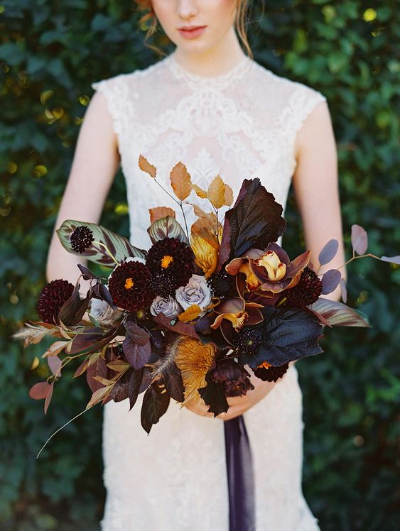 a moody luxurious wedding bouquet with dark leaves, blooms, dried leaves and some herbs