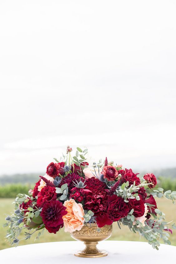 a super bold wedding centerpiece with burgundy and fuchsia blooms, peachy flowers, thistles and greenery