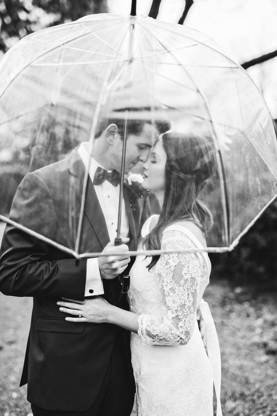 a transparent umbrella will let catch the couple at their best even on a rainy day