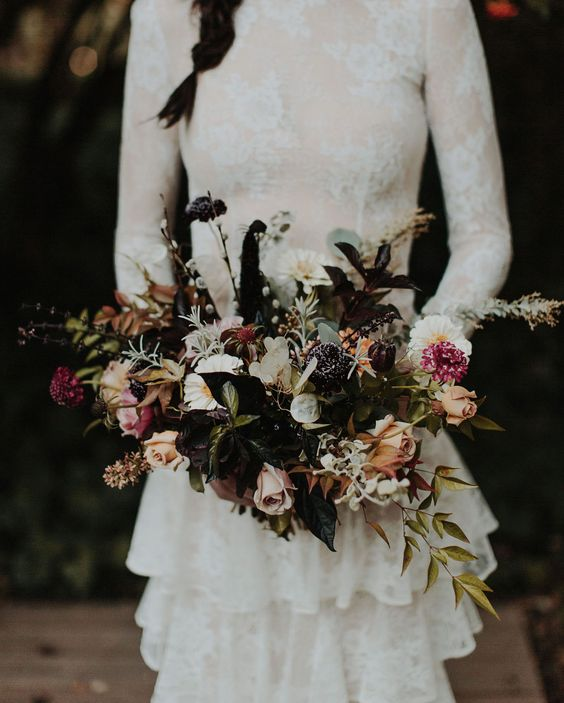 a whimsy Halloween bouquet with foliage and herbs, dark and just moody blooms is a piece of art