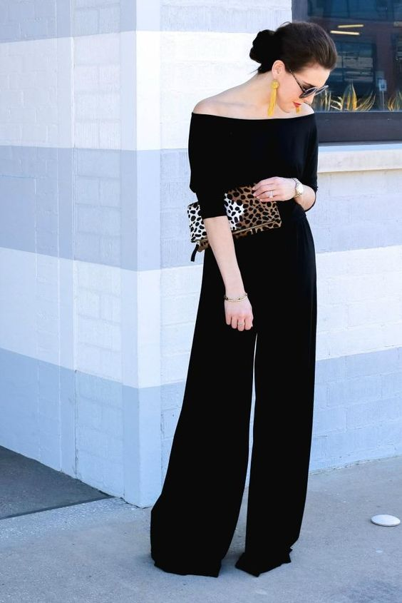 an off the shoulder black jumpsuit with wideleg pants, a leopard clutch and tassel earrings is a timeless solution