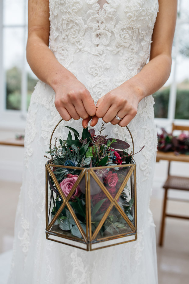 The bride was rocking a lantern filled with flowers and greenery instead of a usual bouquet
