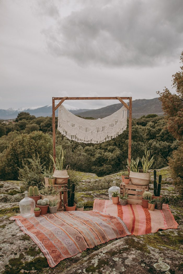 The ceremony space was done with a wooden arch with macrame, rugs and potted succulents and greenery