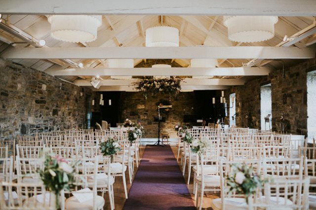 The ceremony space was done with white chairs and lush greenery and blooms