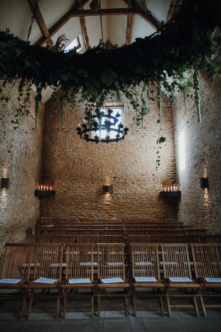 The ceremony took place indoors, the space was decorated with lush greenery hangings and candles