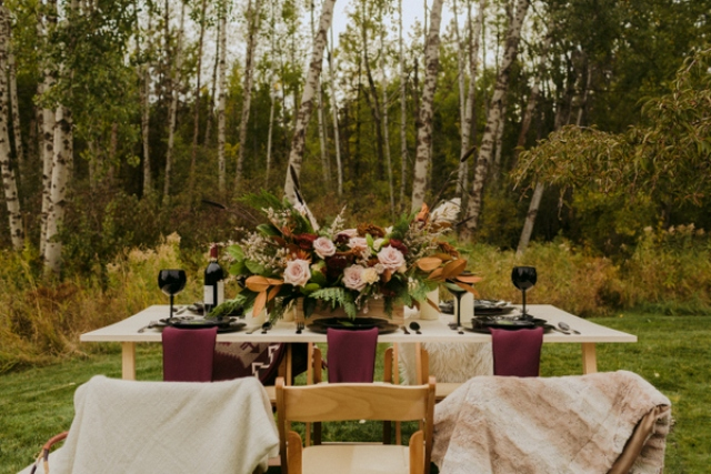 The table was set right on a lawn, the chairs were covered with faux fur and blankets