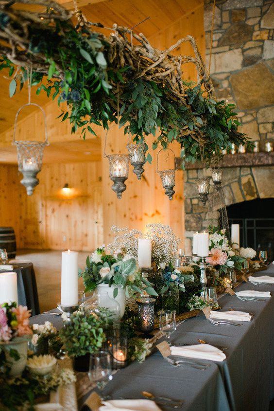 a dried branches and greenery wedding decoration with candle lanterns for a secret garden wedding