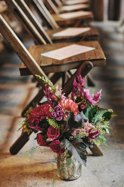 a moody floral arrangement in a mercury glass vase, dark pink, grey, yellow and purple for a moody fall wedding
