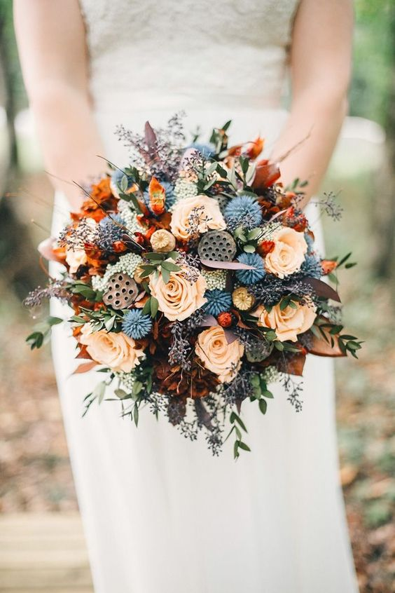 a moody round wedding bouquet done in orange, rust, grey, lilac and with blue touches plus some wildflowers