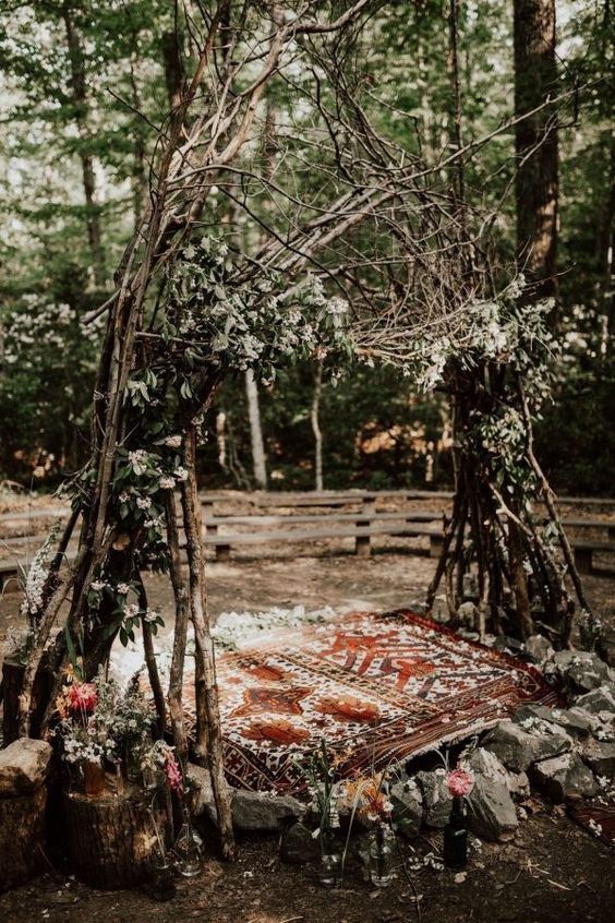 a really woodland wedding arch of branches, greenery, blooms, with a rug and stones for a boho wedding
