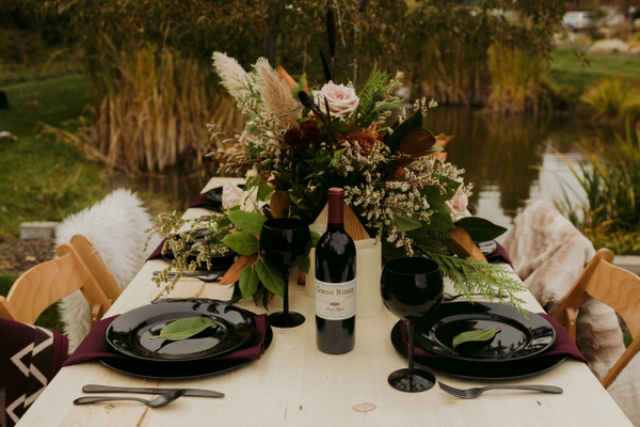 The table setting was done with dramatic black glasses and plates, with an uncovered table and a lush floral centerpiece