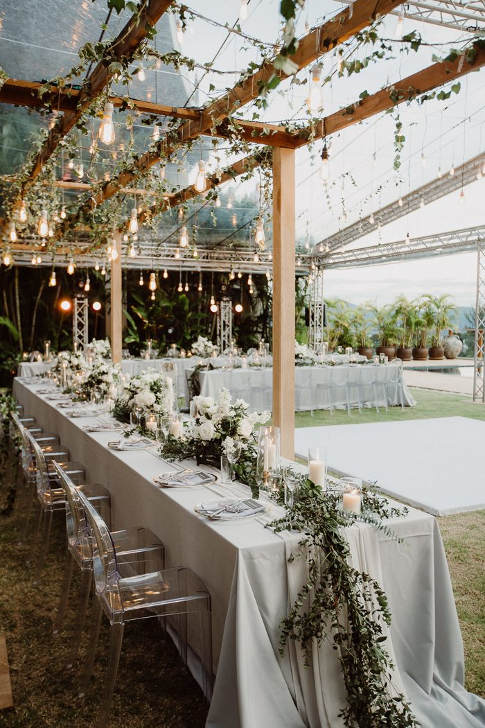 The wedding reception space was done with a lot of greenery, lush white blooms, candles and bulbs