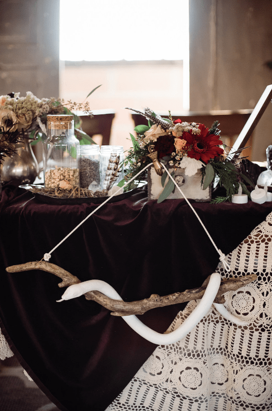 The wedding venue was a barn decorated in boho woodland style, with feathers, antlers, blooms and greenery