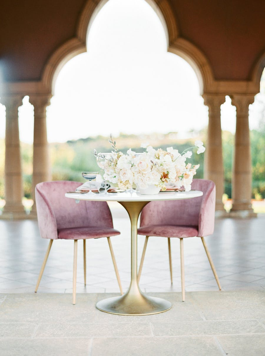 There was a sweetheart table done with a gold leg and dusty pink chairs with gold legs