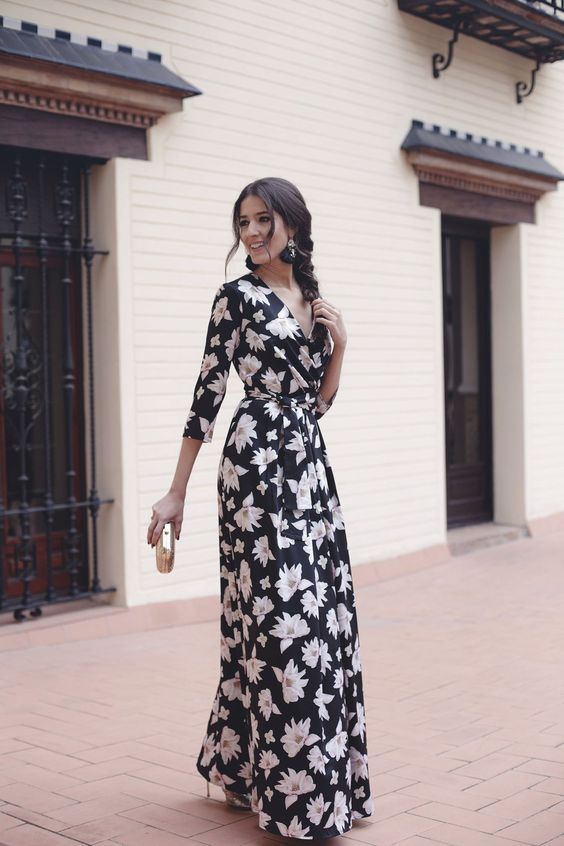 a black floral maxi dress with long sleeves and a V-neckline, black tassel earrrings, metallic shoes and a clutch
