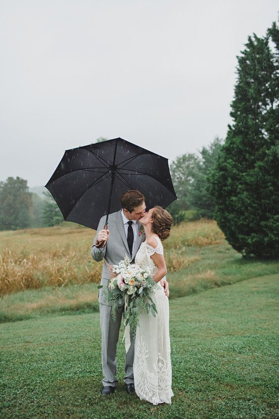 a black umbrella makes the neutrally dressed couple stand out with its contrasting shade