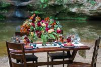 07 a bright-toned jewel tablescape with a lush floral centerpiece and lanterns plus colored glasses
